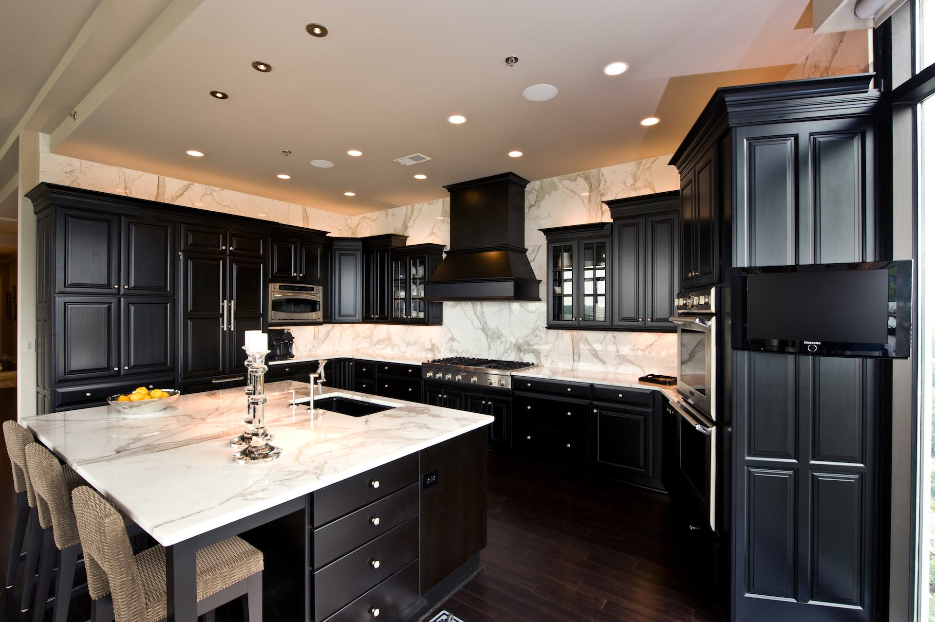 calacatta gold countertops and backsplash with black cabinets