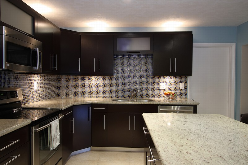 white countertop and mosaic backsplash and dark chocolate cabinets