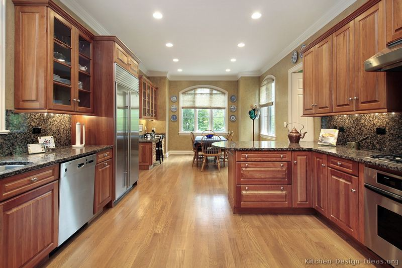 baltic brown granite countertop with medium wood cherry cabinets ands light oak flooring