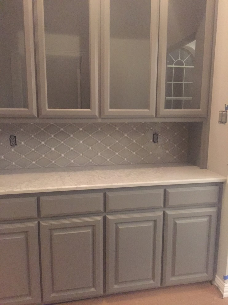 Gray kitchen cabinets with Mountblanc Countertop and diagonal gray backsplash tiles