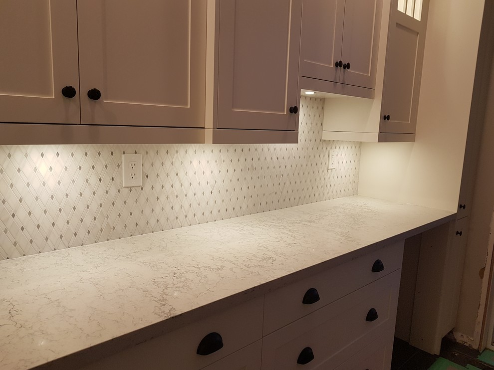 Mountblanc Countertop with white cabinets and diagonal marble backsplash